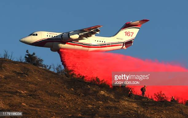 An air tanker drops fire retardant over power lines while helping to fight the Hillside Fire in the North Park neighborhood of San Bernardino...