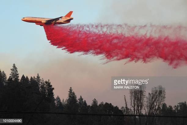 TOPSHOT An air tanker drops fire retardent to try to contain flames from the Carr fire as it spreads towards the town of Lewiston near Redding...