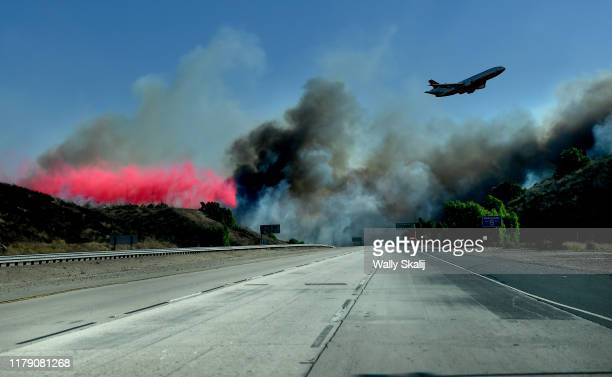 An air tanker drops phoschek near the 23 Freeway as firefighters make a stand and prevent the Easy Fire from burning into Moorpark in Simi Valley...