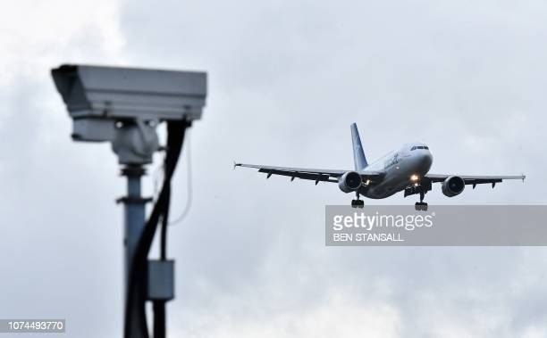 An Air Transat aircraft is pictured beyond a CCTV camera as it prepares to land at London Gatwick Airport south of London on December 21 as flights...