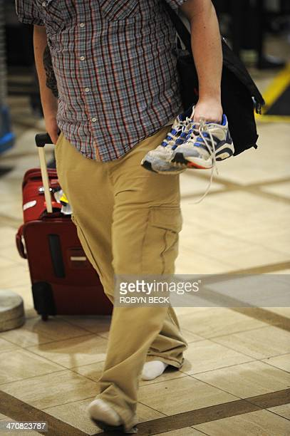 An air traveler carries his shoes after passing through the Transportation Security Administration security check at Los Angeles International...