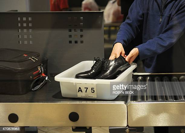 An air traveler places his shoes in a bin before passing through the Transportation Security Administration security check at Los Angeles...