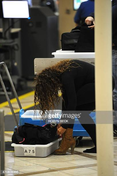 An air traveler puts her shoes back on after passing through the Transportation Security Administration security check at Los Angeles International...