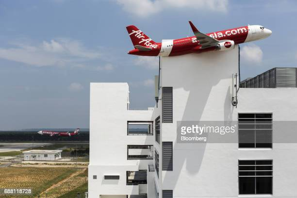 An AirAsia Bhd aircraft left lands at Kuala Lumpur International Airport 2 next to the company's headquarters building in Sepang Selangor Malaysia on...