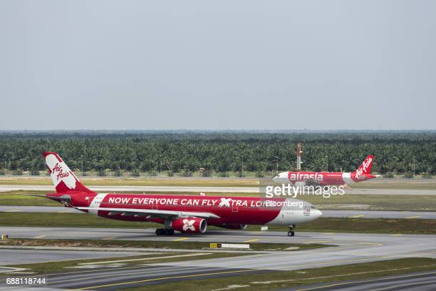 An AirAsia Bhd aircraft right prepares to take off as an AirAsia X Bhd aircraft taxis on the tarmac at Kuala Lumpur International Airport 2 in Sepang...