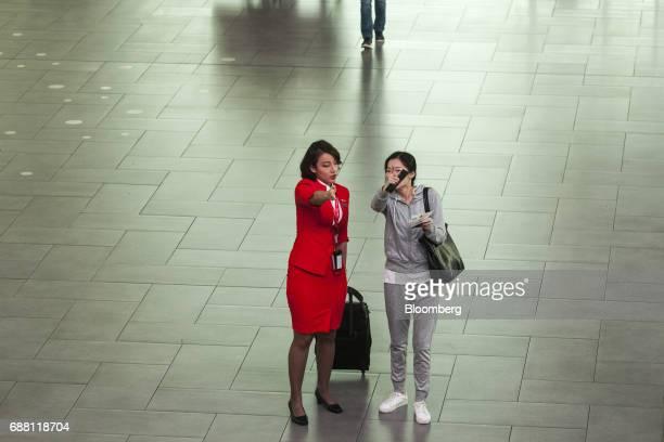 An AirAsia Bhd flight attendant directs a passenger at Kuala Lumpur International Airport 2 in Sepang Selangor Malaysia on Thursday May 25 2017...