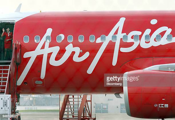 An AirAsia Bhd stewardess waves from an AirAsia Airbus parked on the tarmac at the Low Cost Carrier Terminal in Kuala Lumpur Malaysia on Saturday...