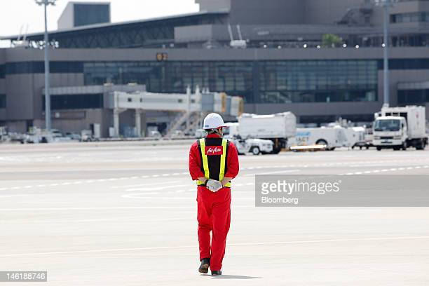 An AirAsia Japan Co engineer walks on the tarmac during a media preview at Narita Airport in Narita City Chiba Prefecture Japan on Monday June 11...