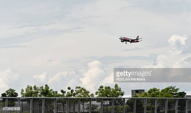 An Airasia passenger jet flies over an industrial park as it prepares to land at Changi International airport in Singapore on April 24 2015 AFP...