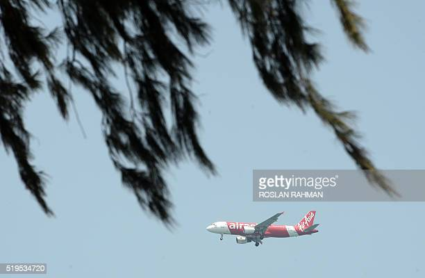 An AirAsia passenger plane prepares to land at Changi International airport in Singapore on April 7 2016 / AFP / ROSLAN RAHMAN