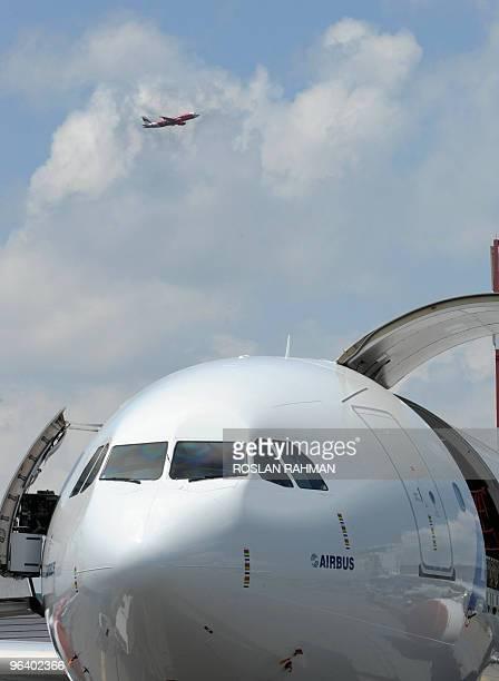 An AirAsia plane is seen after taking off from Changi international airport as an Airbus A330200 plane is on display at the Singapore Airshow in...