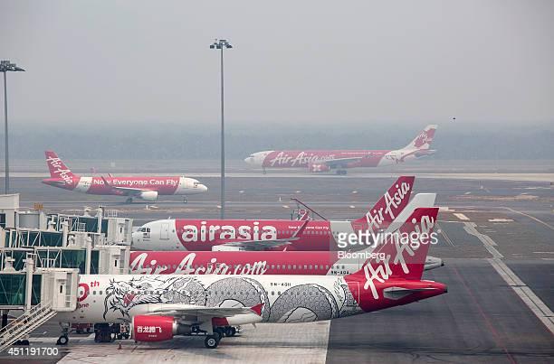 An AirAsia X Bhd aircraft taxi on the runway rear as AirAsia Bhd aircraft stand at boarding gates at Kuala Lumpur International Airport 2 in Sepang...