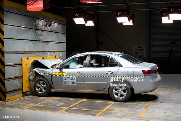 An airbag is deployed in front of a crash test dummy inside a Hyundai Motor Co NF Sonata vehicle during a headon crash test at 48 kilometers per hour...