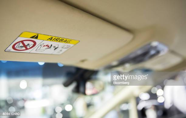 An airbag warning label is displayed on a sun visor of a Toyota Motor Corp vehicle at the Toyota Mega Web showroom in Tokyo Japan on Tuesday Aug 1...