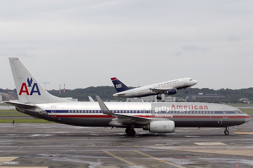 An Airbus A319, operated by US Airways Group Inc., takes off behind a Boeing Co. 737, operated by AMR Corp.'s American Airlines, at Reagan National Airport in Washington, D.C., U.S., on Tuesday, May 8, 2012. American Airlines gave more details of its strategy as US Airways Group Inc. steps up pressure for a possible takeover bid. Photographer: Andrew Harrer/Bloomberg via Getty Images