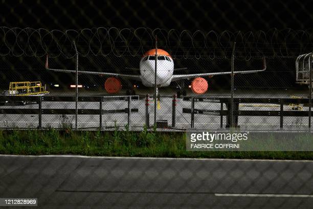 An Airbus A320 commercial plane of low cost airline EasyJet is parked with its jet engines covered due to flight interruption amid the COVID19...