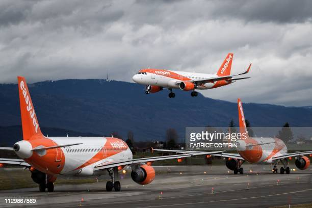 An Airbus A320 commercial plane with registration GEZRU of carrier EasyJet is seen landing above two other planes to the lowcost company at Geneva...
