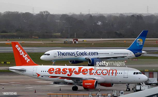 An Airbus A320214 aircraft operated by EasyJet Plc stands near a terminal gate while a Boeing 757200 aircraft operated by Thomas Cook Group Plc taxis...