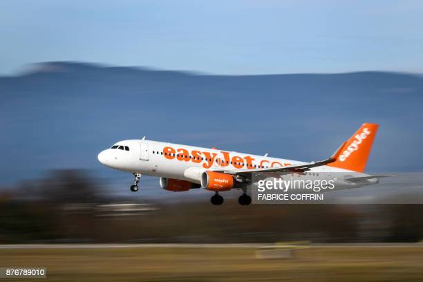 An Airbus A320214 commercial plane registration GEZWJ of lowcost carrier EasyJet is seen landing at Geneva Airport on November 20 2017 in Geneva