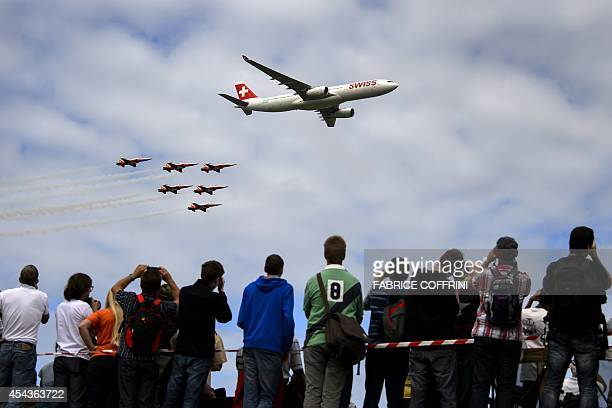 An Airbus A330 commercial plane of Swiss International Air Lines flights with fighter jets of the Patrouille Suisse during the first day of AIR14...