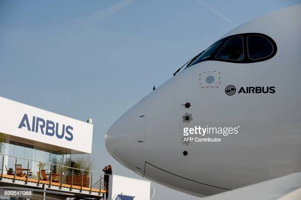 An Airbus A350-1000 is parked on the tarmac in front of the Airbus pavilion at Le Bourget on June 22, 2017 during the International Paris Air Show. /...