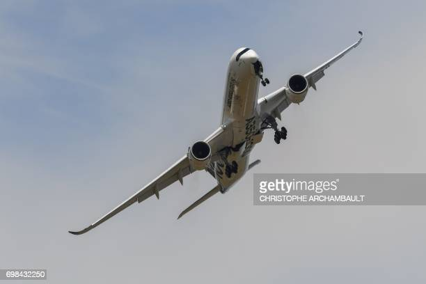 An Airbus A3501000 XWB jet airliner performs its show flight during the International Paris Air Show at Le Bourget north of Paris on June 20 2017 /...