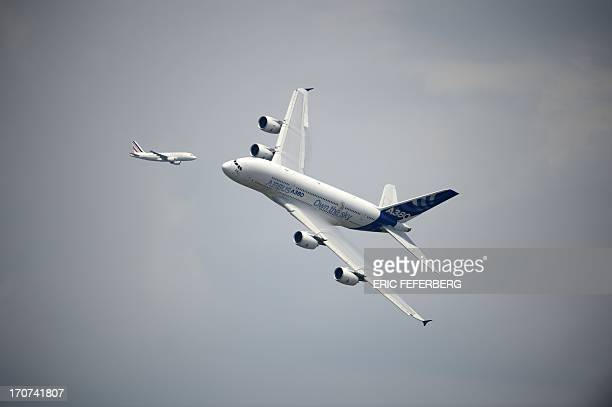 An Airbus A380 aircraft flies over Le Bourget airport on June 17, 2013 on the opening day of the International Paris Air show. AFP PHOTO / ERIC...