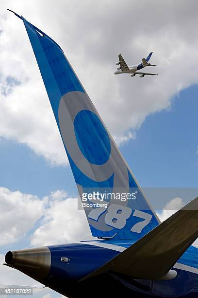 An Airbus A380 aircraft produced by Airbus Group NV flies above the tail fin of a Boeing 7879 Dreamliner aircraft produced by Boeing Co during an...