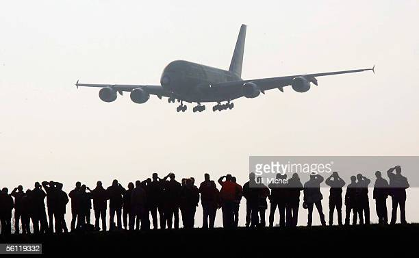 An Airbus A380 the world's largest commercial airliner is watched by spectators as it approaches Hamburg Germany on November 8 coming from Toulouse...