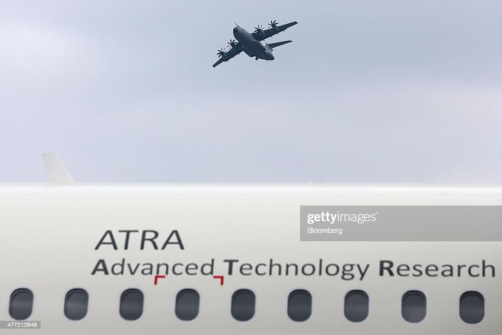An Airbus A400M military aircraft performs a flight demonstration above an Airbus A320 Advanced Technology Research Aircraft (ATRA) on the opening day of the 51st International Paris Air Show in Paris, France, on Monday, June 15, 2015. The 51st International Paris Air Show is the world's largest aviation and space industry exhibition and takes place at Le Bourget airport June 15 - 21. Photographer: Jasper Juinen/Bloomberg via Getty Images