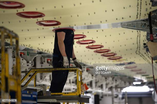 An Airbus employee constructs a wing for an Airbus A350 aircraft at Airbus' wing production plant near Broughton in northeast Wales on December 1...