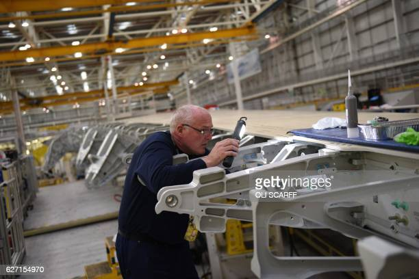 An Airbus employee performs an inspection of the construction of a wing for an Airbus A350 aircraft at Airbus' wing production plant near Broughton...
