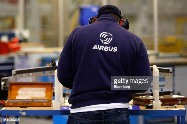 An Airbus logo sits on an employee's top as he works on a section of wing inside the A320/A330 wing assembly building at the Airbus Group NV assembly...