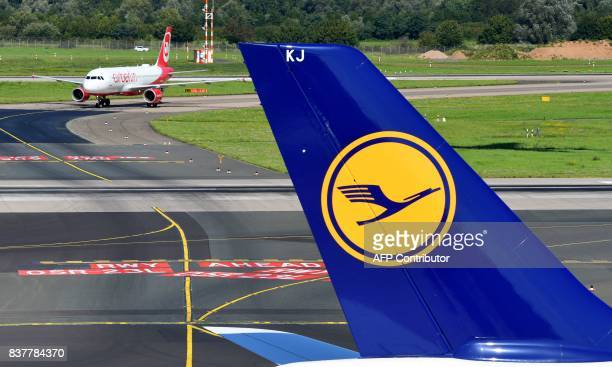 An Airbus operated by German airline 'Air Berlin' rolls on the runway behind an airplane operated by Lufthansa on August 23 2017 in Duesseldorf...