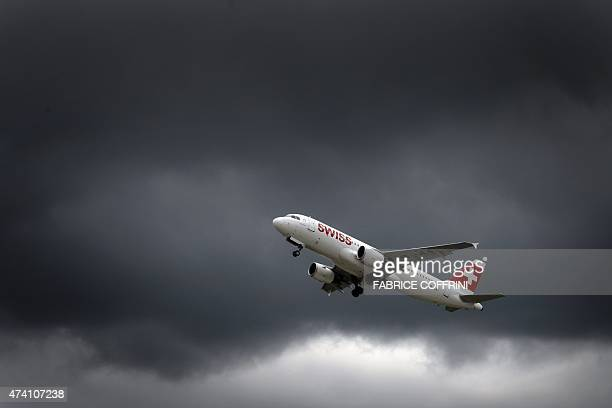 An Airbus plane of Swiss International Air Lines takes off under heavy clouds on May 19, 2015 in Geneva. AFP PHOTO / FABRICE COFFRINI