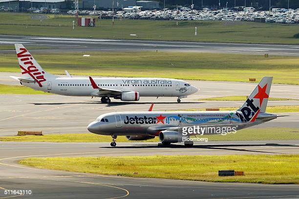 An Airbus SAS A321 aircraft operated by Jetstar Airways the budget arm of Qantas Airways Ltd front and a Boeing Co 737800 aircraft operated by Virgin...