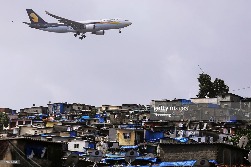 An Airbus SAS A330-202 aircraft operated by Jet Airways India Ltd. flies over slum housing as it approaches to land at Chhatrapati Shivaji International Airport in Mumbai, India, on Saturday, June 27, 2015. Jet Airways is India's Second biggest airline by market share according to the Indian Aviation Ministry. Photographer: Dhiraj Singh/Bloomberg via Getty Images