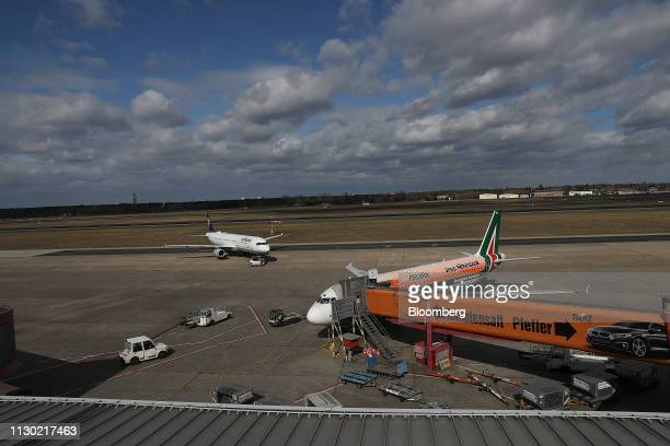 An Airbus SE A320 aircraft operated by Alitalia SpA sits connected to a passenger walkway at Tegel airport in Berlin Germany on Wednesday March 13...