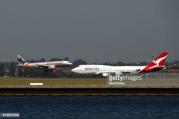 An Airbus SE A320200 aircraft operated by Jetstar Airways the budget arm of Qantas Airways Ltd left lands as a Boeing Co 747 aircraft operated by...