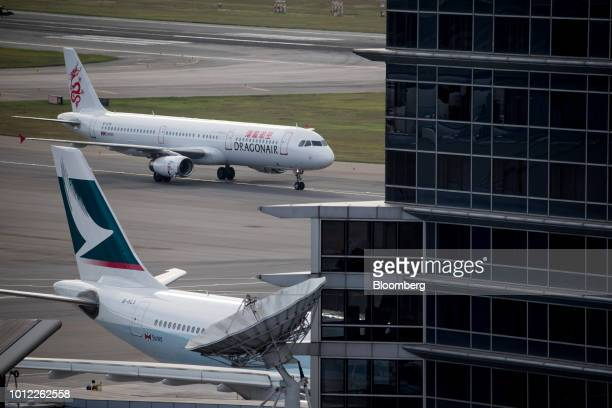 An Airbus SE A321 aircraft operated by Cathay Dragon a unit of Cathay Pacific Airways Ltd top taxis past an Airbus A330 aircraft operated by Cathay...