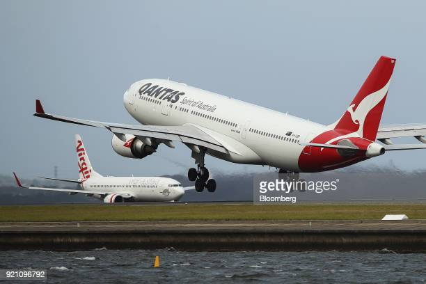 An Airbus SE A330300 aircraft operated by Qantas Airways Ltd right takes off as an aircraft operated by Virgin Australia Holdings Ltd taxies on the...