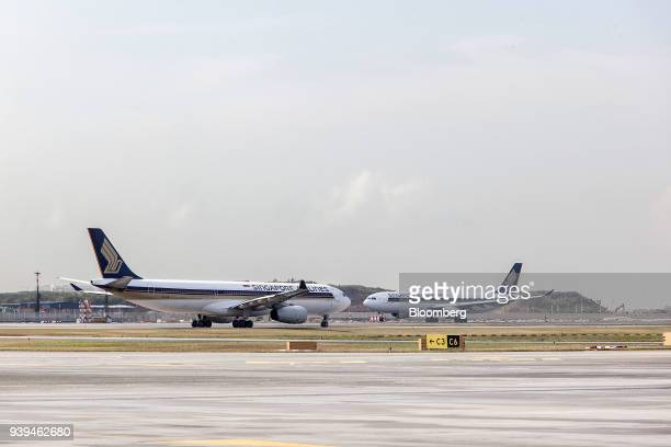 An Airbus SE A330343 aircraft operated by Singapore Airlines Ltd left taxies along the tarmac past another Singapore Air aircraft at Changi Airport...