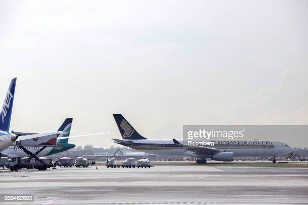 An Airbus SE A330343 aircraft operated by Singapore Airlines Ltd right taxies along the tarmac at Changi Airport in Singapore on Wednesday March 28...