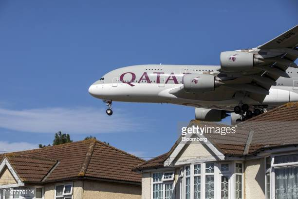 An Airbus SE A380 passenger aircraft, operated by Qatar Airways, passes residential rooftops as it prepares to land at London Heathrow Airport in...