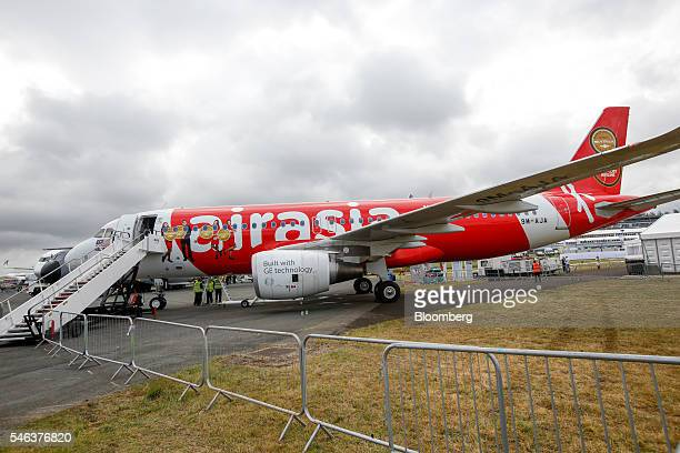 An Airbus SE Airbus A320 aircraft operated by AirAsia Bhd sits on display on the second day of the Farnborough International Airshow 2016 in...