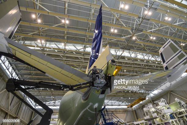 An Airbus technician works on the rear fuselage and tail on the assembly line of the Airbus Beluga XL large transport aircraft on March 20 2018 in...