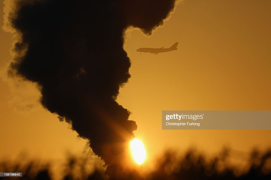 An aircaft makes its approach to Manchester Airport as cold weather accentuates the steam from a grass dryer in the Cheshire countryside on December 11, 2012 in Knutsford, England. Forecasters are warning that the UK could experience the coldest day of the year so far tomorrow, as temperatures could drop as low as -14C, bringing widespread ice, harsh frosts and freezing fog. Travel disruption is expected with warnings for heavy snow.