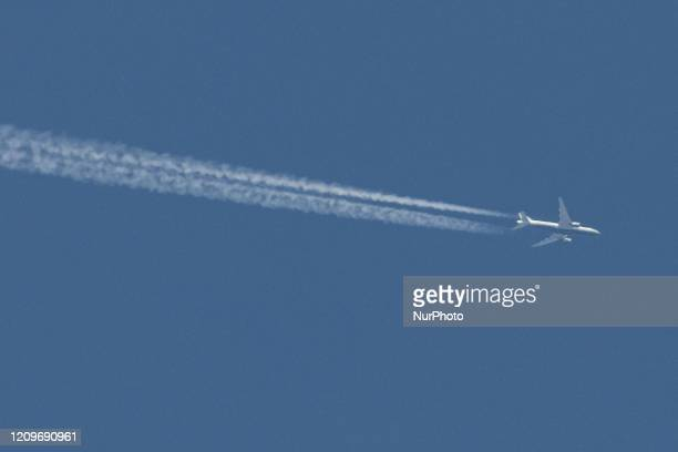 An aircraft as seen flying over Thessaloniki Greece on April 11 2020 in the clear blue almost summer sky The airplane leaves contrails or chemtrails...