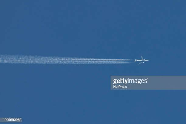 An aircraft as seen flying over Thessaloniki, Greece on April 11, 2020 in the clear blue almost summer sky. The airplane leaves contrails or...