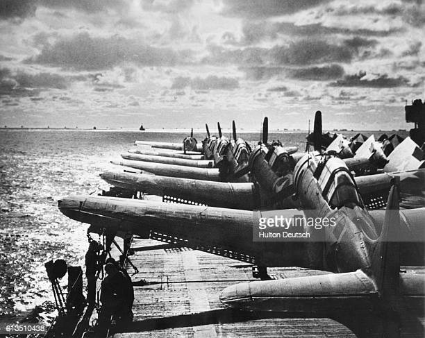 An aircraft carrier packed with Douglas Dauntless divebombers and a Grumman fighter plane heads a convoy of some twenty vessels bound for the war...